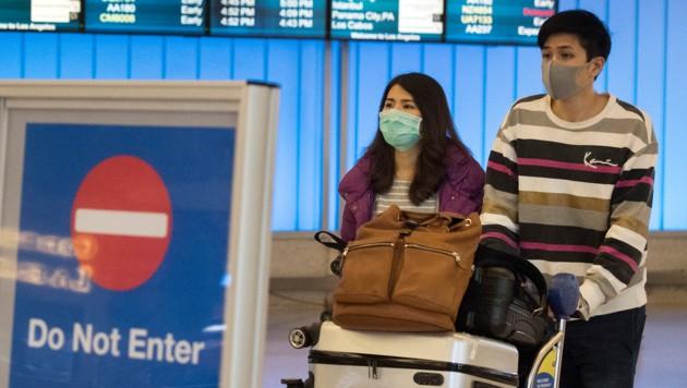 Chinesische Passagiere nach ihrer Landung in Los Angeles (Bild: APA/AFP/Mark RALSTON)