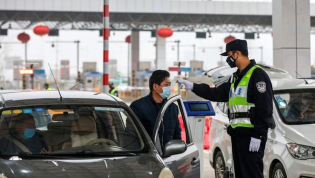Temperaturkontrolle an einem Checkpoint in Wuhan (Bild: AP)
