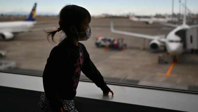 Ein Kind mit Schutzmaske auf einem Flughafen in Japan (Bild: AFP)