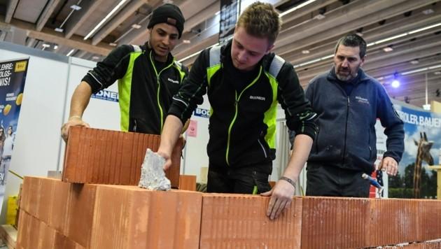Die Maurer René Sehabi (li.) und Nicklas Asslaber arbeiten am Stand der Tiroler Bauakademie unter der Aufsicht von Georg Mair (re.). (Bild: LIEBL Daniel | zeitungsfoto.at)