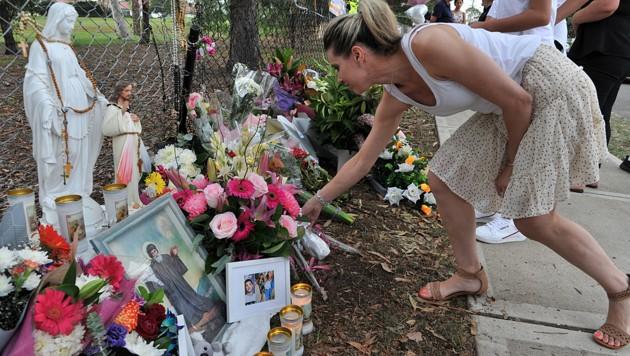 Menschen legen am Unfallort Blumen nieder. (Bild: AFP)
