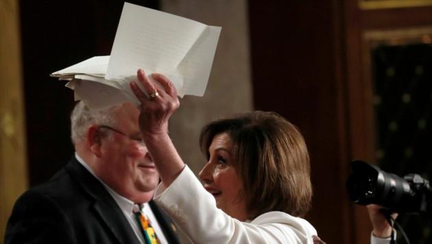 Stolz präsentierte Pelosi nach vollbrachter Tat die zerrissenen Seiten. (Bild: APA/AFP/GETTY IMAGES/POOL)