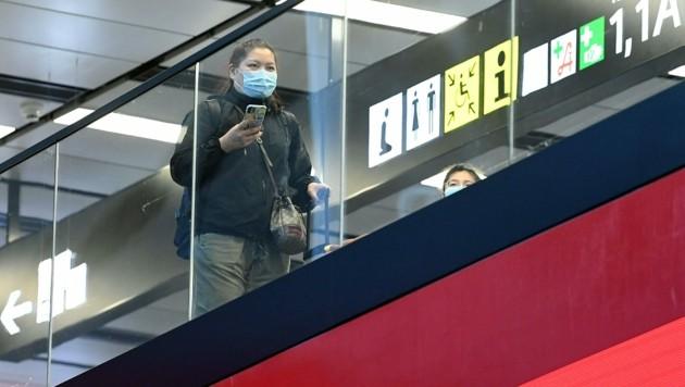 Ein Passagier mit Schutzmaske am Flughafen Wien-Schwechat (Bild: APA/Helmut Fohringer)