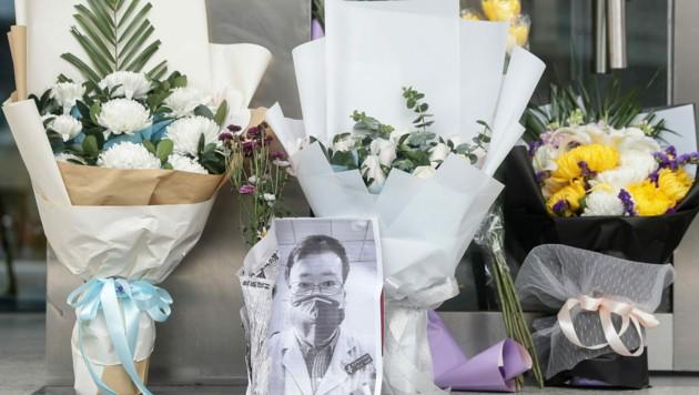 Bild und Blumen erinnern vor dem Spital an Wenliang. (Bild: AFP)