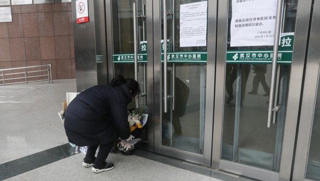Eine Bewohnerin Wuhans legt Blumen für den verstorbenen Mediziner vor dem Eingang des Krankenhauses ab. (Bild: AFP)
