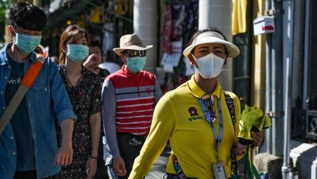 Chinesische Touristen mit Schutzmasken in Bangkok (Bild: APA/AFP/Lillian SUWANRUMPHA)