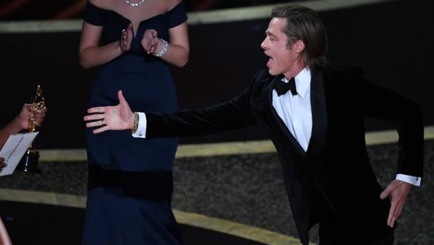 Brad Pitt schien es gar nicht erwarten zu können, seinen Oscar endlich in Händen halten zu dürfen. (Bild: AFP)