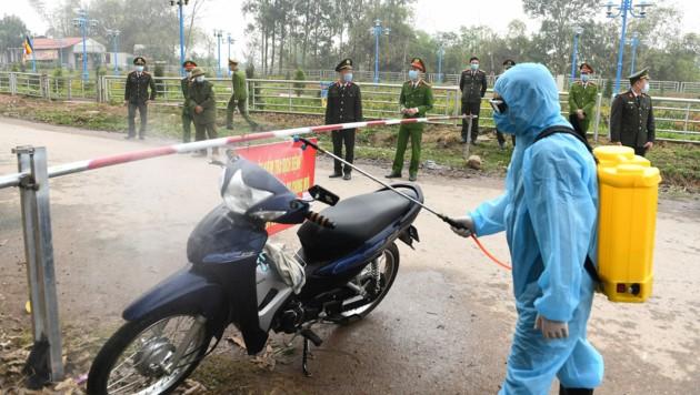 In Vietnam wurden mehrere Dörfer unter Quarantäne gestellt. Behördenvertreter in Schutzanzügen sprühen durchfahrende Fahrzeuge mit Desinfektionsmittel ein. (Bild: AFP)