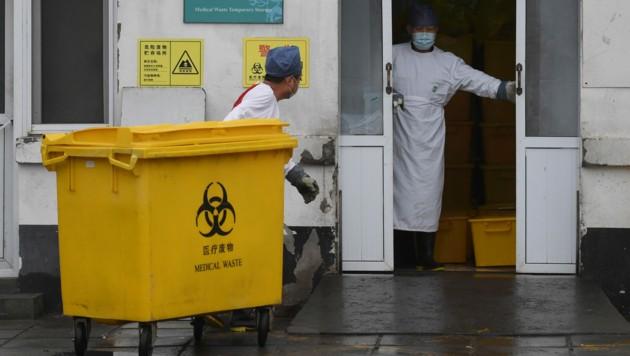 Mitarbeiter eines Krankenhauses in Peking bei der Entsorgung medizinischer Abfälle (Bild: AFP)