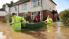 Zahlreiche Menschen mussten mit Booten aus ihren Häusern gerettet werden. Die Hochwassersituation könnte noch viel schlimmer werden. Es werden neue Regenfälle erwartet. (Bild: APA/AFP/Oli SCARFF)