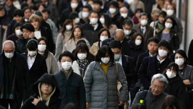 Menschen in Tokio - nur die wenigsten tragen keine Atemschutzmasken. (Bild: AP)
