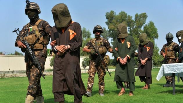 Afghanische Soldaten führen gefangen genommene Talibankämpfer ab. (Bild: APA/AFP/NOORULLAH SHIRZADA)