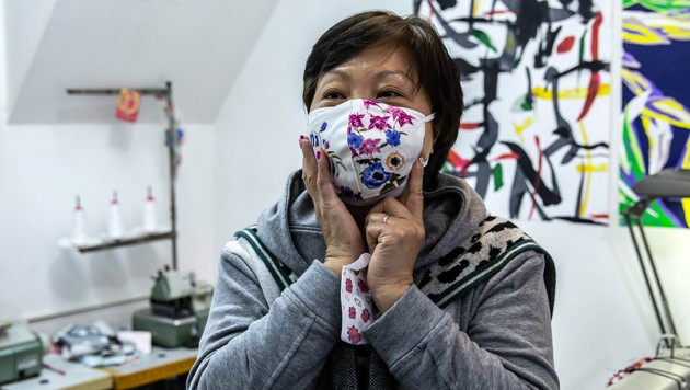 Elase Wong präsentiert eine von ihr geschneidert Atemschutzmaske (Bild: AFP/Isaac Lawrence)