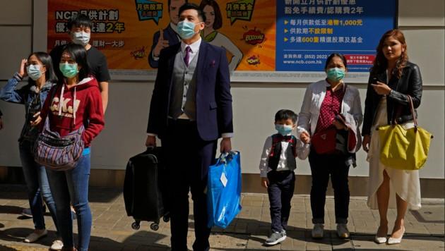 Trotz des Coronavirus versuchen die Menschen in China, wie hier in Hongkong, einem halbwegs geregelten Tagesablauf nachzugehen. (Bild: AP)
