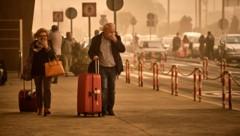 Fluggäste am Flughafen Santa Cruz de Tenerife schützen sich mit Tüchern vor dem feinen Sand. (Bild: Associated Press)