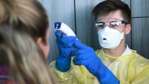 Ein Sanitäter misst mit einem Infrarot-Thermometer die Körpertemperatur einer Person. (Bild: APA/HELMUT FOHRINGER)