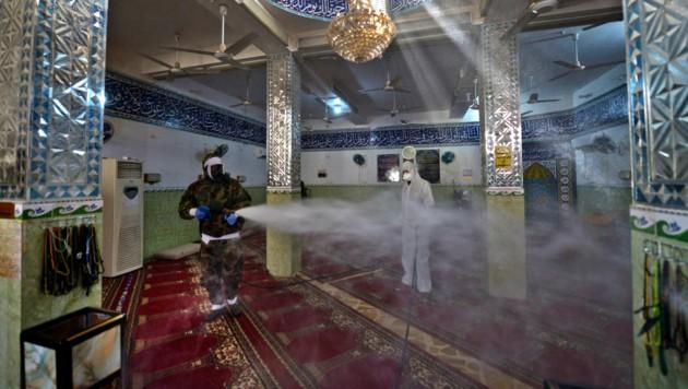 Im Irak desinfizieren Männer eine Moschee.