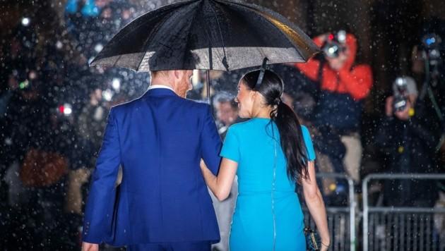 Im strömenden Regen posierten Prinz Harry und Herzogin Meghan geduldig für die Fotografen. (Bild: AFP )
