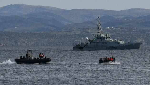 Migranten auf dem Weg nach Lesbos, im Hintergrund die HMC Valiant, die im Auftrag von Frontex patrouilliert (Bild: AFP)