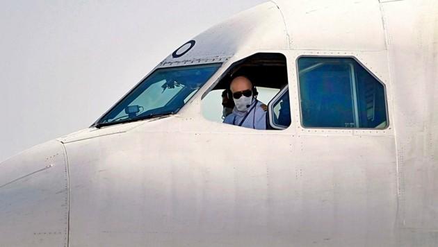 Der Pilot einer iranischen Maschine fliegt mit Schutzmaske. (Bild: AP)