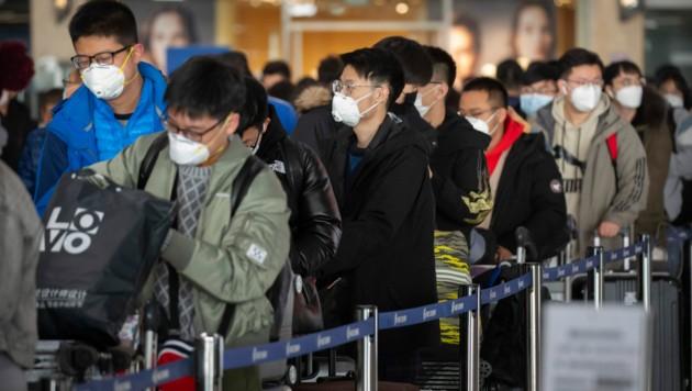 Reisende am Flughafen von Peking (Bild: AP)