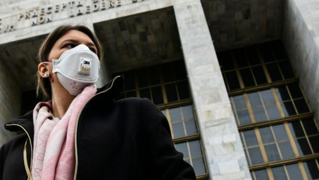 Eine Frau mit Schutzmaske vor dem Justizpalast in Mailand (Bild: AFP)