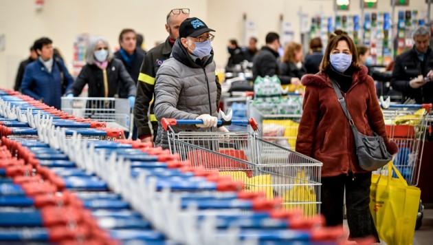 In Italien müssen Menschen in Supermärkten Schutzmasken tragen. (Bild: AP)