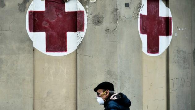 Ein Mann geht mit Gesichtsmaske an einem Krankenhaus in Turin vorbei. (Bild: AFP)