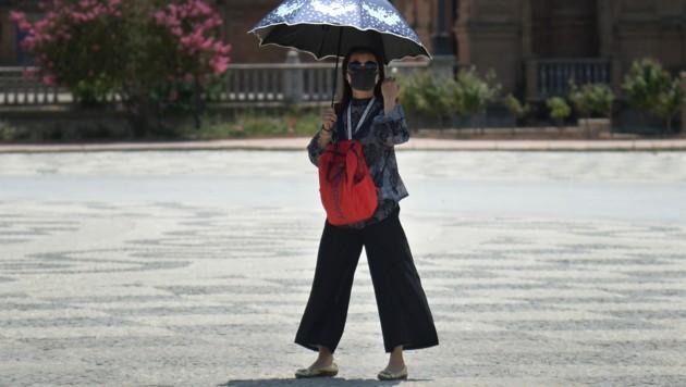 Eine Touristin in Sevilla schützt sich mit einem Sonnenschirm vor dem für diese Jahreszeit ungewöhnlich warmen Wetter in Andalusien. (Bild: AFP )