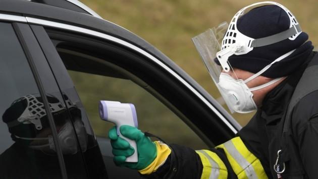 Ein tschechischer Polizist überprüft die Temperatur eines Autofahrers, der von Deutschland nach Tschechien einreisen möchte. (Bild: AFP)