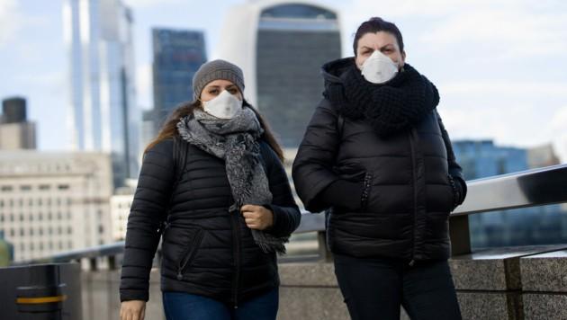 Passantinnen mit Gesichtsmasken in London (Bild: AFP)