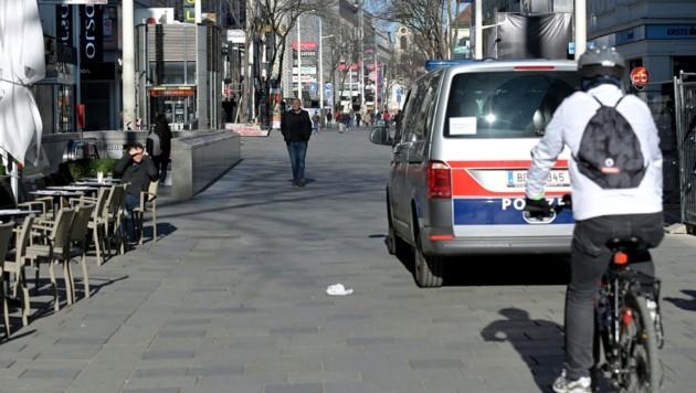 Die Polizei patrouilliert auf der - nicht ganz menschenleeren - Mariahilfer Straße in Wien. (Bild: APA/HERBERT P. OCZERET)