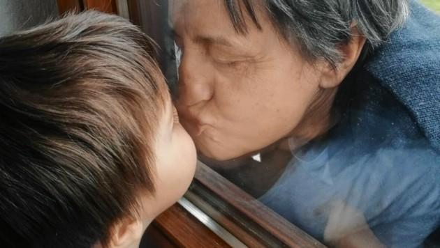 """Bilder, die berühren: Wie Großeltern geschützt werden und trotzdem ein liebevoller Austausch stattfinden kann - die Familie Maier aus Silberegg teilte diesen ganz besonderen Moment mit unserer """"Krone""""-Redaktion. (Bild: Familie Maier)"""