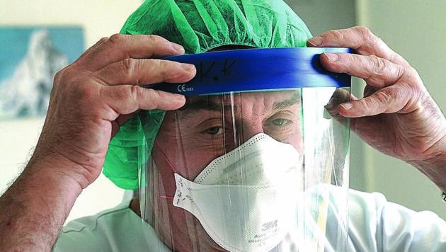 Infektionsexperte Andreas Kapper beim Anlegen der Schutzbekleidung. (Bild: Sepp Pail)