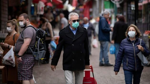 Menschen mit Atemschutzmasken auf einem Markt in Tel Aviv (Bild: AP)
