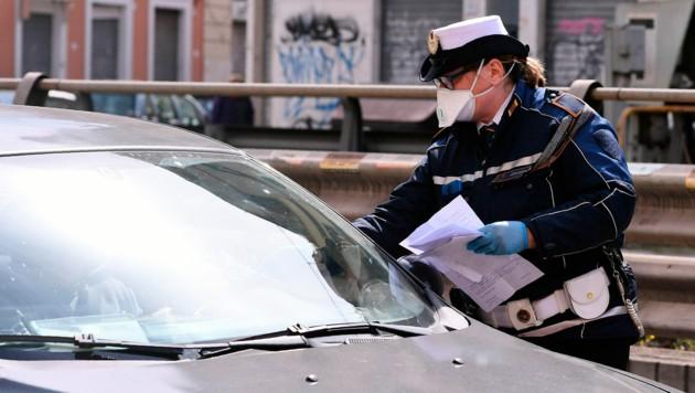 Die Polizei in Italien hält Autos an und kontrolliert, ob die Lenker einen triftigen Grund haben, um draußen unterwegs zu sein. Dazu gehören beispielsweise der Einkauf von Lebensmitteln oder Medikamenten. (Bild: LaPresse)