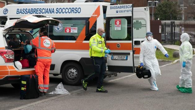 Ärztliches Personal bereitet sich darauf vor, einen Covid-19-Patienten entgegenzunehmen, der gerade mit dem Hubschrauber in das Krankenhaus von Brescia gebracht wird. (Bild: AP)