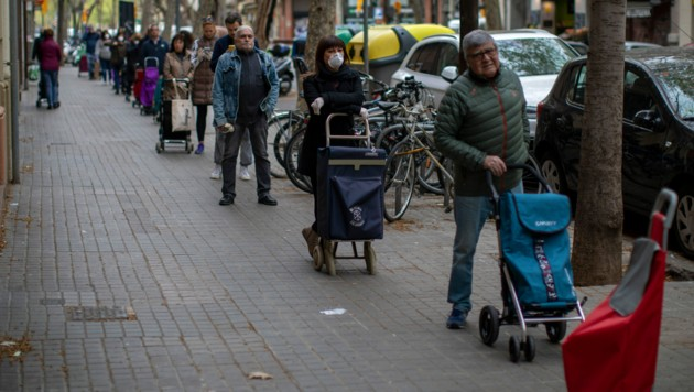 Eine Menschenschlange vor einem Geschäft in Barcelona (Bild: The Associated Press)