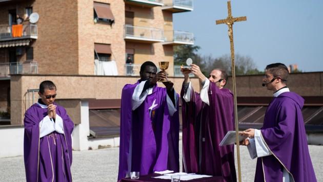 """Vier Priester feiern am """"Sonntag der Tränen"""" die Heilige Messe am Dach einer römischen Kirche. (Bild: APA/AFP/Tiziana FABI)"""