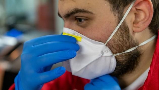 Ein Sanitäter des Roten Kreuzes mit Schutzmaske (Bild: APA/JAKOB GRUBER)