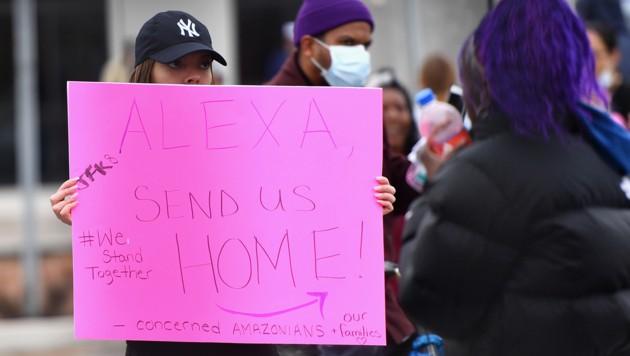 """Mit Slogans wie """"Alexa, schick uns heim!"""" warben Amazon-Mitarbeiter für strengere Maßnahmen gegen Covid-19. (Bild: APA/AFP/Angela Weiss)"""