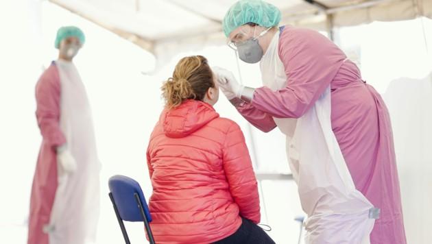 Schutzkleidung entnimmt bei einer Fußgängerin im Coronavirus-Testzentrum eine Probe. (Bild: APA/dpa/Uwe Anspach)