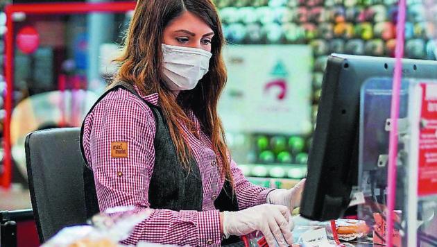 In Hinkunft alltäglich: Die Dame an der Kasse trägt Mund-Nasen-Schutz, Handschuhe und ist durch Plexiglas abgeschirmt. (Bild: Markus Wenzel)