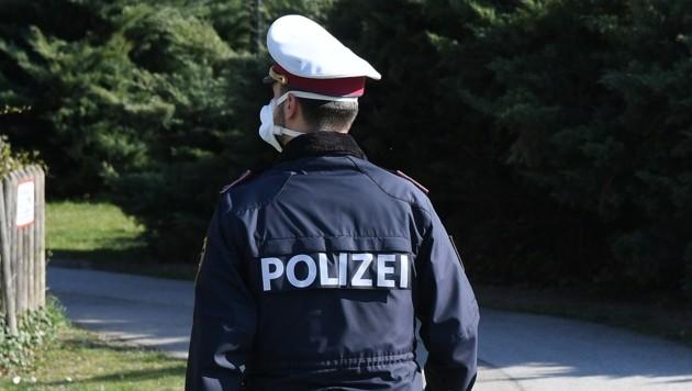 Ein Polizist mit Mundschutz (Bild: P. Huber)