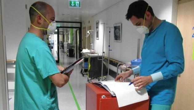 """Michael Müller (links) und Patrick Morre bei einer Besprechung über den Zustand ihrer derzeit etwa 60 Patienten. """"Bald"""", prognostizieren sie, """"wird unsere Station voll belegt sein."""" (Bild: Uniklinikum Salzburg)"""