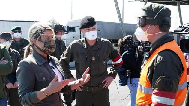 Ministerin Klaudia Tanner mit Tarnmaske im Gespräch mit einem Assistenzsoldaten in Nickelsdorf, begleitet von Militärkommandant Gasser. (Bild: Reinhard Judt)