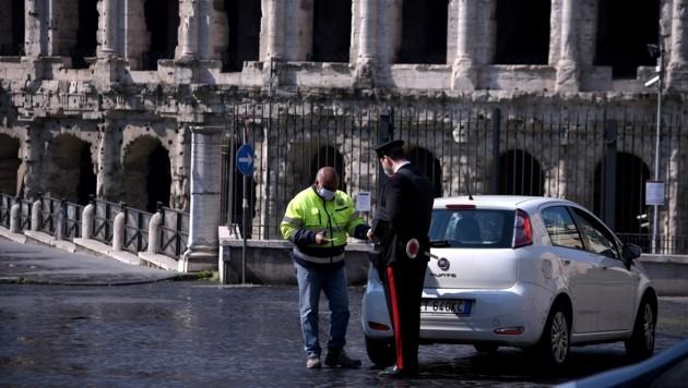 Ein Polizist bei einer Verkehrskontrolle in Rom (Bild: AFP)