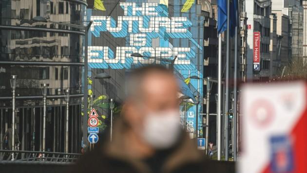Ein Mann mit Maske vor dem Gebäude der EU-Kommission in Brüssel (Bild: AFP)