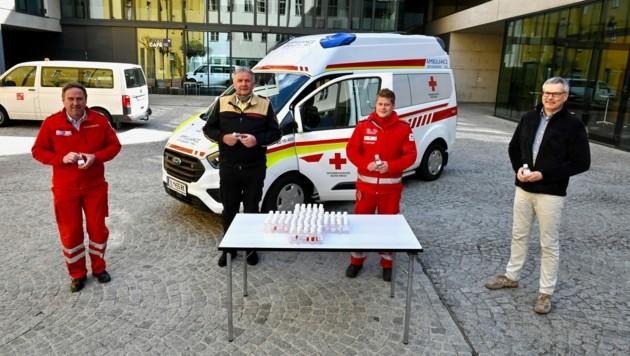 Desinfektionsmittelübergabe: Hubert Huppertz (rechts) übergibt das Desinfektionsmittel an die Einsatzkräfte. (Bild: RK Tirol/Daniel Liebl)