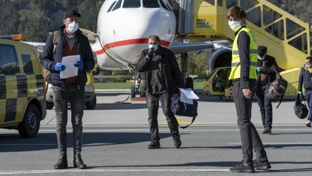 Mit dem gebotenen Abstand verließen die rumänischen Fachkräfte das Flugzeug. (Bild: Land Tirol/Berger)
